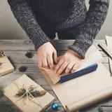 Męskie ręki zawijają Bożenarodzeniowego prezent na drewnianym stole Obraz Stock