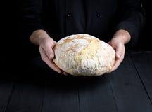 Męskie szef kuchni ręki trzymają całego bochenek piec wokoło chleba fotografia stock