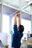 Męskie wykonawcze rozciąganie ręki przy jego biurkiem Fotografia Royalty Free