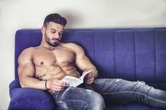 Męskiego bodybuilder czytelnicza książka na kanapie Obrazy Stock