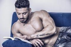 Męskiego bodybuilder czytelnicza książka na kanapie Obraz Royalty Free