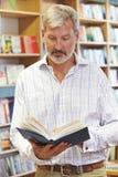 Męskiego klienta Czytelnicza książka W Bookstore Fotografia Royalty Free