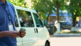 Męskiego kuriera odliczający pieniądze otrzymywający dla drobnicowej dostawy, cogodzinna zapłaty usługa zdjęcia royalty free