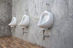 Męskiego pisuaru sanitarny artykuły w biurowym nowożytnym loft obraz stock