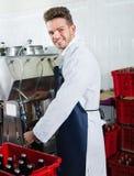 Męskiego pracownika rozlewniczy wino z maszyną przy iskrzastego wina fabryką Zdjęcie Royalty Free