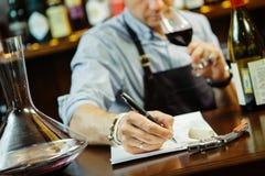 Męskiego sommelier smaczny czerwone wino i robić przy baru kontuarem notatki zdjęcie stock
