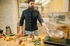 Męskiego szefa kuchni kulinarny mięso z vetables w nieckę obrazy royalty free