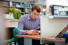 Męskiego ucznia czytelnicza książka w bibliotece uniwersyteckiej Zdjęcie Stock