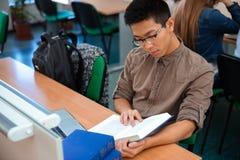 Męskiego ucznia czytelnicza książka w sala lekcyjnej Zdjęcie Royalty Free
