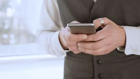 Męskiego ucznia pozycja okno i texting od smartphone, patrzeje dla pracy obraz stock