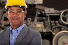 Męskiej inżynier odzieży żółty hełm z maszyną w tle Zdjęcie Stock