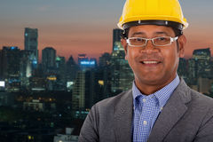Męskiej inżynier odzieży żółty hełm z miasta światła tłem Obraz Royalty Free
