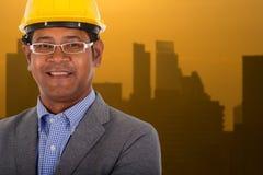 Męskiej inżynier odzieży żółty hełm z miasta światła tłem Zdjęcia Royalty Free
