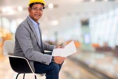 Męskiej inżynier odzieży żółty hełm z plamy tłem Zdjęcie Stock