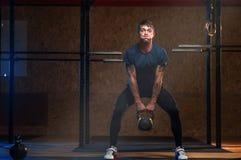 Męskiej mięśniowej atlety podnośny kettlebell Obrazy Stock