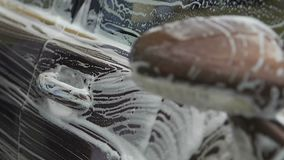 Męskiej ręki płuczkowy luksusowy samochód z foamy gąbką, kierowca bierze opiekę pojazd zbiory