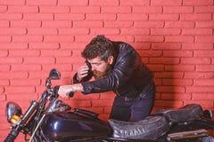 Męskości pojęcie Mężczyzna z brodą, rowerzysta w skórzanej kurtki blisko silnika rowerze w garażu, ściana z cegieł tło modniś fotografia royalty free