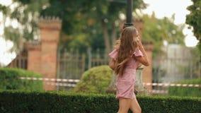 Młoda ładna żeńskiego ucznia mienia książka i przypadkowo puka z młodego człowieka opuszczać podczas gdy biegający na parkowym pa zbiory wideo
