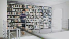 Młoda ładna amerykanin afrykańskiego pochodzenia kobieta jest czytelniczej książki whlie pozycją przed półkami w bibliotece