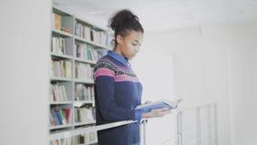Młoda ładna amerykanin afrykańskiego pochodzenia kobieta w nowożytnej bibliotece