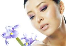 Młoda ładna azjatykcia kobieta z kwiatu purpurowym irysem zamkniętym w górę odosobnionego zdroju, kobieta dnia pojęcie zdjęcia royalty free
