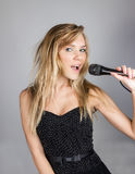 Młoda ładna blond kobieta śpiewa w mikrofonie Zdjęcia Royalty Free
