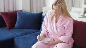Młoda ładna blondynka planuje jej weekendss i pisze liście zakupów zbiory