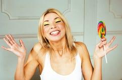 Młoda ładna blondynki dziewczyna z kolorowego cukierku szczęśliwy ono uśmiecha się, emot zdjęcia royalty free