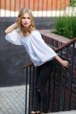 Młoda ładna blondynki kobieta pozuje na schody outdoors fotografia stock