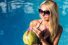 Młoda ładna blondynki kobieta w pływackim basenie z kokosowym koktajlem Fotografia Stock
