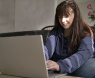 Młoda ładna brunetka ono uśmiecha się podczas gdy pisać na maszynie na laptopie obraz stock
