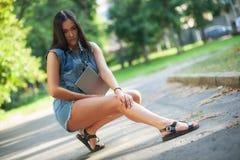 Młoda ładna brunetki dziewczyna w drelichowych skrótach z pastylką siedzi na słuchaniu i drodze muzyka na ulicie fotografia stock