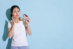 Młoda ładna dziewczyna patrzeje słodkiego smakowitego pączek zdjęcia stock