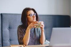 młoda ładna dziewczyna pije gorącej herbaty z cytryną dla laptopu zdjęcia stock