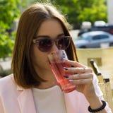 Młoda ładna dziewczyna pije zimnego napój, plenerowego Zdjęcie Royalty Free