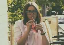 Młoda ładna dziewczyna pije zimnego napój, plenerowego Zdjęcia Stock
