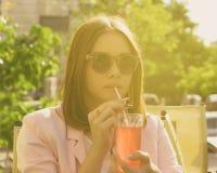 Młoda ładna dziewczyna pije zimnego napój, plenerowego Zdjęcia Royalty Free
