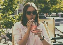 Młoda ładna dziewczyna pije zimnego napój, plenerowego Obrazy Stock