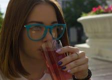 Młoda ładna dziewczyna pije zimnego napój, plenerowego Fotografia Stock