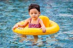 Młoda ładna dziewczyna w żółtym dopłynięcie pierścionku w basenie z jasnym watem Obrazy Stock