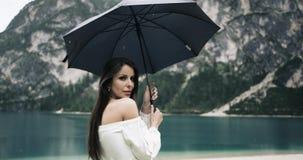 Młoda ładna kobieta bawić się z jej parasolem na plaży zadziwiający jezioro i patrzeje kamera zbiory wideo