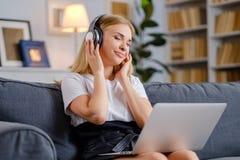 Młoda ładna kobieta cieszy się muzykę z hełmofonami fotografia stock