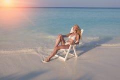Młoda ładna kobieta garbnikuje w plażowym krześle w morzu, tonuje obraz royalty free