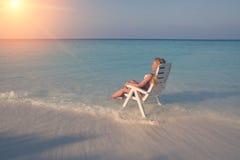 Młoda ładna kobieta garbnikuje w plażowym krześle w morzu, tonuje obrazy royalty free