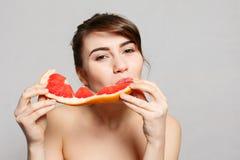 Młoda ładna kobieta lub śliczna seksowna dziewczyna z długie włosy chwytów grapefruitowym owocowym plasterkiem Obraz Royalty Free