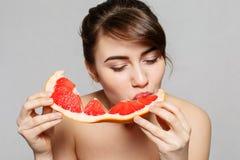 Młoda ładna kobieta lub śliczna seksowna dziewczyna z długie włosy chwytów grapefruitowym owocowym plasterkiem Obraz Stock