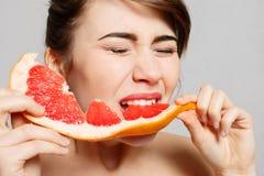 Młoda ładna kobieta lub śliczna seksowna dziewczyna z długie włosy chwytów grapefruitowym owocowym plasterkiem Zdjęcia Stock
