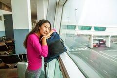 Młoda ładna kobieta patrzeje w okno w lotniskowym czekaniu jej lot zdjęcie stock