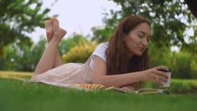 Młoda ładna kobieta pije kawę na trawie w lato parku zbiory