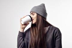 Młoda ładna kobieta pije kawę od papierowej filiżanki w popielatym stroju Takeaway pakunku projekta układ Zdjęcia Royalty Free
